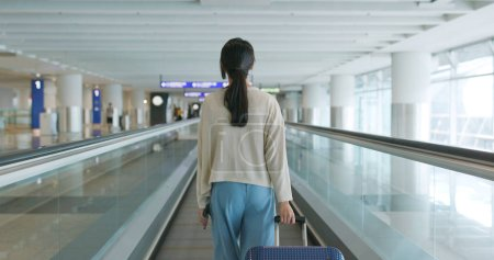 Woman go for a trip with her luggage at Hong Kong airport