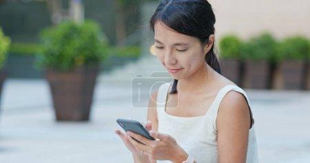 Photo pour Jeune femme à l'aide de téléphone portable à l'extérieur - image libre de droit