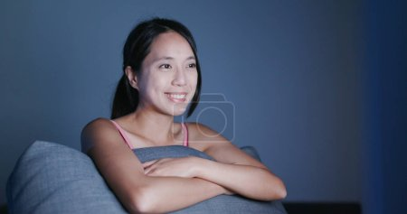 Cheerful Woman watching video on computer at night