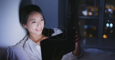 Woman watching on digital tablet at night