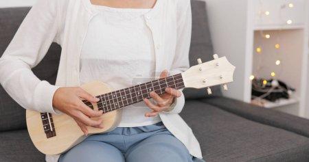 Photo pour Femme joue une chanson sur ukulele - image libre de droit
