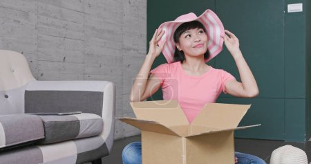 Woman unpacking parcel at home, online shopping concept