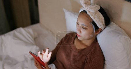 Photo pour Femme appliquer le masque sur le lit et à l'aide de téléphone portable pendant la nuit - image libre de droit