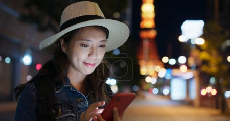 Woman use of mobile phone in Tokyo city at night