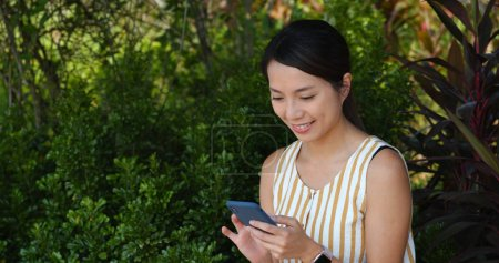 Photo for Woman use of mobile phone with the green background - Royalty Free Image