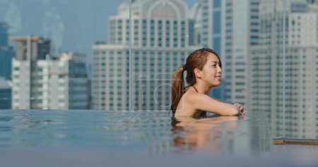 Photo pour Femme à la piscine à débordement en ville - image libre de droit