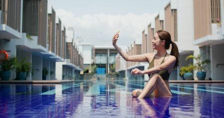 Photo for Woman take phone on mobile phone at swimming pool - Royalty Free Image