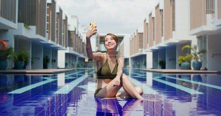 Photo pour Femme prendre selfie sur téléphone portable à la piscine - image libre de droit