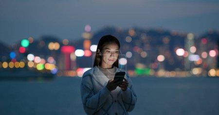 Photo pour Femme regarde le téléphone portable dans la ville la nuit - image libre de droit