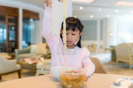 Photo for Kid girl eat instant noodles - Royalty Free Image