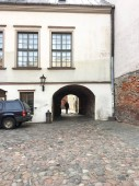 Entrance courtyard with an arch and cobblestone pavement in old