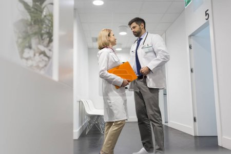 Photo for Low angle view of doctors discussing in corridor at hospital - Royalty Free Image