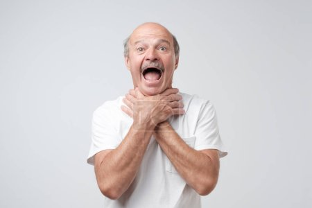 Mature european man in white tshirt shouting and suffocate because painful strangle. Health problem. Asphyxiate and breathing problem concept.