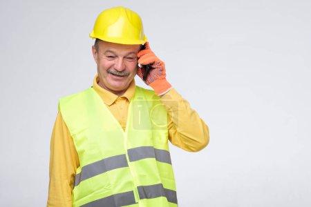 Photo pour Réparateur hispanique aîné dans le casque protecteur parlant sur son téléphone avec le client. - image libre de droit