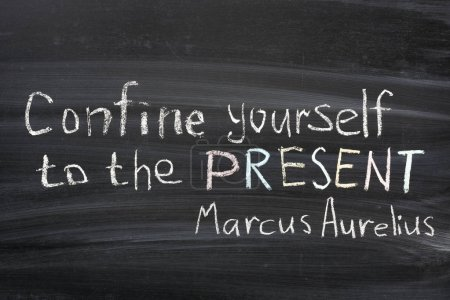 """Photo for Famous Marcus Aurelius quote """"Confine yourself to PRESENT"""" handwritten on blackboard - Royalty Free Image"""