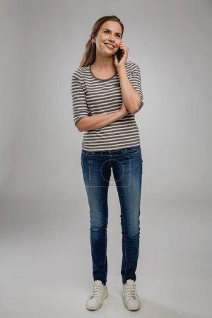Photo pour Portrait de belle jeune femme heureuse sur un fond gris parlant au phon - image libre de droit
