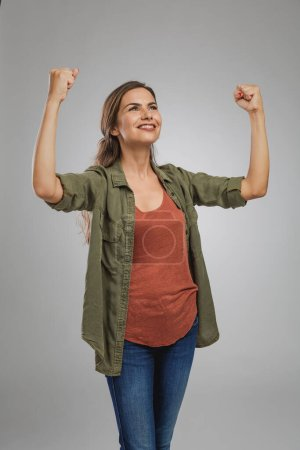Photo for Beautiful and successful young woman with arms raised - Royalty Free Image