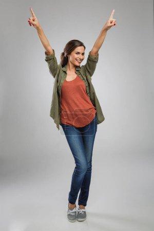 Photo pour Belle et confiante jeune femme sur fond gris en studio, les mains en l'air - image libre de droit