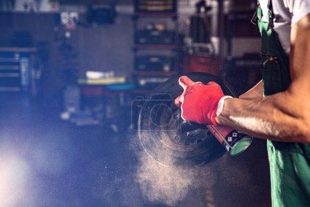 Car mechanic lubricates the bearing with a aerosol...