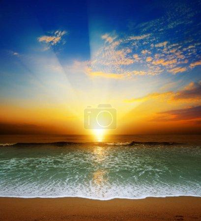 Photo pour Coucher de soleil fantastique sur l'océan, les vagues de mer et le sable. - image libre de droit