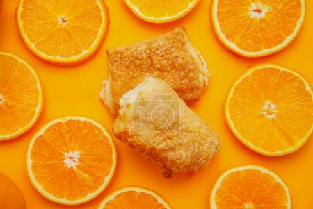 Photo for Homemade appetizing pies made of puff pastry with orange filling on an orange background - Royalty Free Image