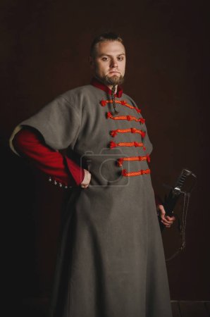 Photo for Portrait of a man in a medieval costume on a dark background. Clothes of the Polish gentry. Proud, strict man starting in a historical costume - Royalty Free Image
