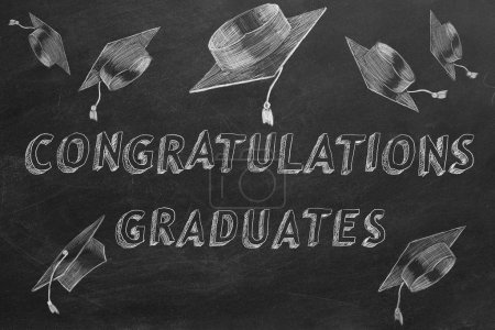 """Photo for Hand drawing text """"congratulations graduates"""" and graduation caps on blackboard. - Royalty Free Image"""