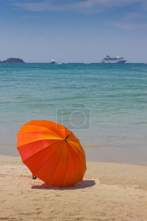 Orange umbrella on the beach in Thailand