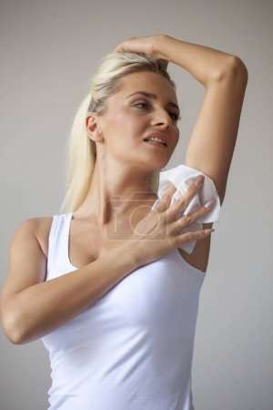 Photo for Blonde woman in white shirt wiping the armpit with wet wipes, perspiration, sweat - Royalty Free Image