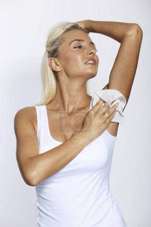 Photo for Woman wiping the armpit with wet wipes, perspiration, sweat remover - Royalty Free Image
