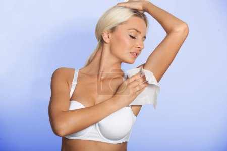 Photo for Higiene - young woman wiping the armpit with wet wipes, perspiration, sweat - Royalty Free Image
