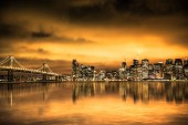 View of San Francisco skyline under golden sunset sky with lights and Bay Bridge