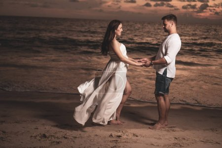 Attractive romantic young couple on the sandy tropical beach during beautiful sunset