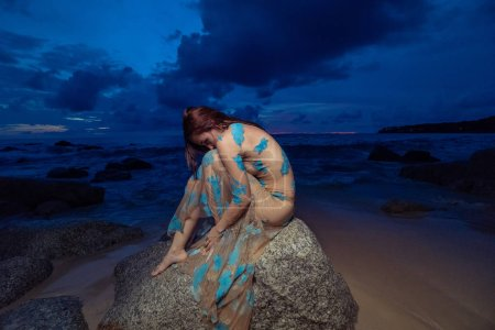 Beautiful mysterious woman in long dress sitting on the rock over sea and cloudy sunset sky background