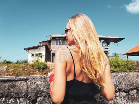 Back view of woman looking at the abandoned building behind barbwire fence in sunny summer day