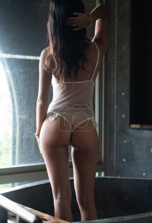 Back view body of fashion model indoors. Beauty brunette woman with attractive body in lace lingerie. Female ass in underwear