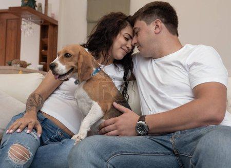 Photo pour Portrait de couple heureux marié et enceinte avec un chien assis sur le canapé à la maison - image libre de droit