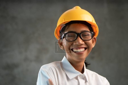 Photo for Portrait of smiling attractive Asian woman engineer over concrete wall background - Royalty Free Image
