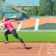 Young female runner at the stadium starts in the s...