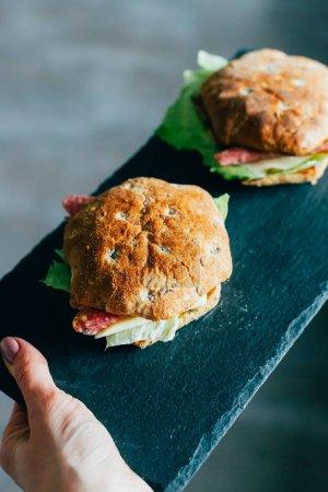 Photo pour Toasts au salami ou jambon, fromage, cornichons, laitue et moutarde sur le tableau de pierre noire - image libre de droit