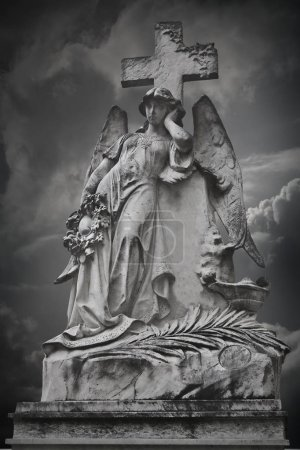 An angel statue with cross and dramatic clouds in ...
