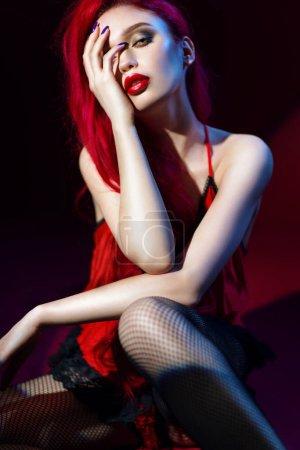 Photo pour Femme séduisante avec les cheveux et les lèvres rouges posant dans la robe rouge de dentelle - image libre de droit