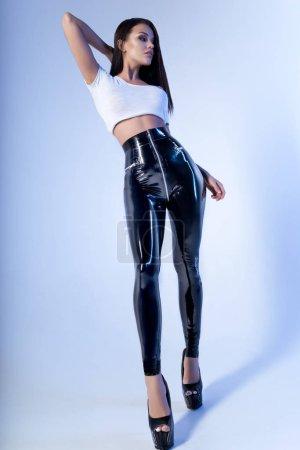 Photo pour Femme sexy de brunette dans le dessus blanc et les leggings de vinyle posant sur le fond léger de studio - image libre de droit