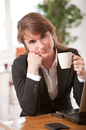 Business woman taking a break from work with a coffee