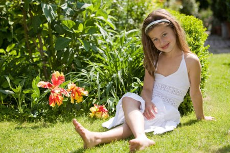 Photo for Beautiful little girl sitting in the grass with a white dress - Royalty Free Image