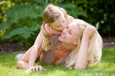 Photo for Pretty blond woman lying in the grass with her daughter, who is giving mum a kiss - Royalty Free Image