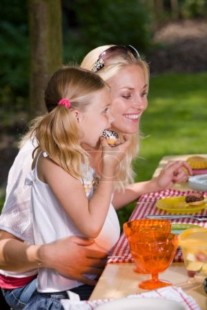 Photo for Adorable mother and daughter eating something outside on a summer's day - Royalty Free Image