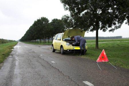 Photo pour La fille vérifie sous le capot de sa voiture alors que le panneau d'avertissement a été mis devant sa voiture - image libre de droit