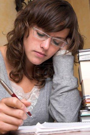 Photo pour Étudiante fatiguée, penchée sur ses livres et son carnet, stylo toujours en main mais sur le point de s'endormir - image libre de droit
