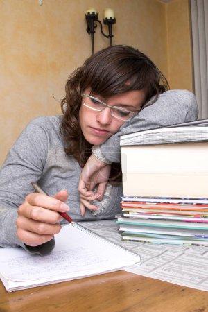Photo pour Étudiante fatiguée penchée sur ses livres regardant toujours ses notes - image libre de droit